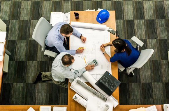 Photo of 3 people looking at some plans at a desk.